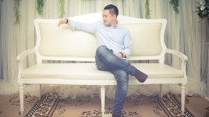 Un homme assis sur un banc fait mine de tenir l'épaule d'une personne imaginaire.