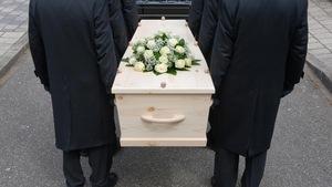 Des porteurs déposent un cercueil dans un corbillard.