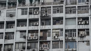 Vue sur un mur de bloc d'appartements muni de nombreux climatiseurs à New Delhi, en Inde.