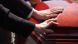 Des gens touchent un petit cercueil lors de funérailles.