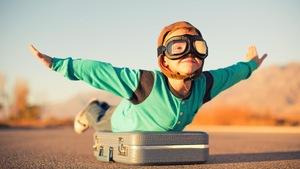 Un petit garçon déguisé en pilote fait mine d'être un avion.