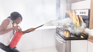 Une femme utilise un extincteur pour contenir un feu de cuisson.