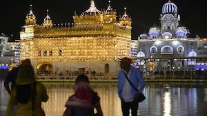 Trois touristes sont devant le Temple d'or, à Amritsar en Inde, le soir.