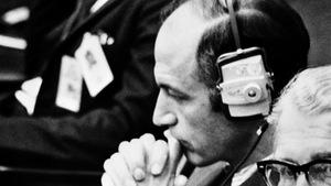 L'administrateur de la NASA George Low portant des écouteurs, les mains portées vers le visage en signe de réflexion.