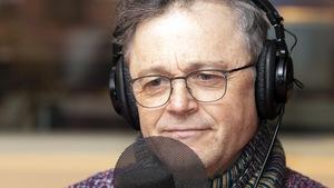 Un homme avec des lunettes est devant un micro.