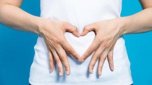 Une femme forme un cœur avec ses mains sur son abdomen.