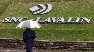 Un homme passe devant le logo de la compagnie SNC-Lavalin.
