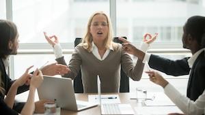 Une femme stressée mime la méditation depuis son bureau, au travail.
