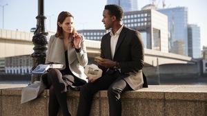 Une femme et un homme en tenue de ville discutent, assis au bord d'un trottoir.