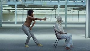 L'artiste Childish Gambino tient un pistolet devant un homme à la tête couverte d'un sac, assis sur une chaise, dans cette omage tirée du vidéoclip de la chanson <i>This Is America</i>.