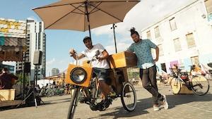 Marcus Freitas (à gauche) et Wallace Roza (à droite) posent fièrement avec leur tricycle conçu pour faire découvrir la musique brésilienne.
