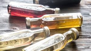 Quatre bouteilles contenant différents vinaigres reposent à l'horizontal sur une table.