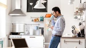 Dans une cuisine, un homme qui a des écouteurs dans les oreilles boit dans une tasse.