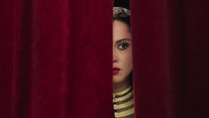 Yasmin Raeis regarde entre deux pans de rideaux dans cette image tirée du film <i>Looking for Oum Kulthum</i>, de Shirin Neshat.