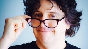 Yves P. Pelletier sourit à la caméra en baissant ses lunettes.