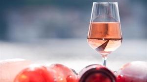 Un verre de vin rosé déposé sur une table.
