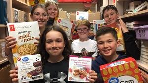Des élèves de l'École élémentaire catholique Pavillon des Jeunes tiennent des boîtes de céréales et de barres tendres.