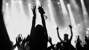 Photo en noir et blanc d'une foule survoltée lors d'un concert de musique.