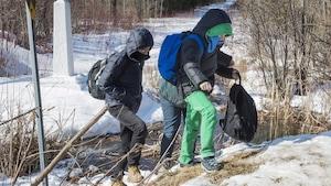 Des migrants traversent illégalement la frontière entre le Canada et les États-Unis afin de demander le statut de réfugié en territoire canadien.