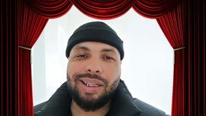 Portrait de Jeanbart avec une demi tuque et des grils, entourés de rideaux rouges de théâtre.