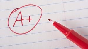 Une feuille d'examen porte la note A+ au stylo-feutre rouge.