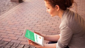 Une lectrice lit son journal hyperlocal sur une tablette.