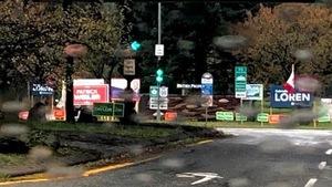 Les pancartes des différents partis se retrouvent sur la pelouse d'un rond-point dont 7 affiches pour la candidate verte.
