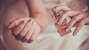 Gros plan sur des mains féminines appliquant un parfum.