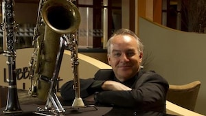 Paul Lamoureux sourit assis à côté d'un saxophone mis sur une table.