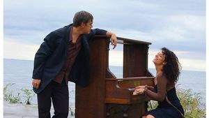 Yves Marchand et Isabelle Cyr sur une plage avec un piano