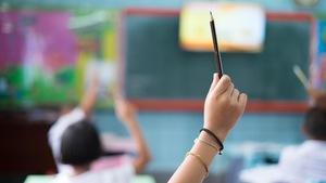 Un enfant dans une salle de classe lève le bras en tenant un crayon dans sa main.
