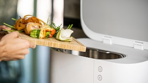 Une personne verse des pelures de légumes dans un bac de compostage qui ressemble à un petit électroménager.