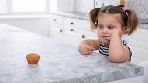 À gauche, un petit gâteau sur un comptoir et, à droite, une jeune fille avec des couettes qui le regarde.