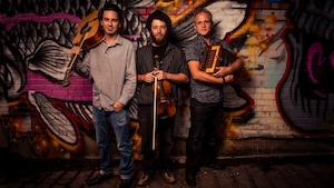 Les trois membres du groupe debout avec leurs instruments.