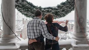 Un couple contemple la vue du balcon de l'Hôtel de Ville en hiver.