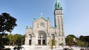 Une place publique devant une église par une journée ensoleillée.