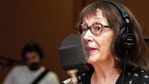 La poète Carole David parle dans un micro.