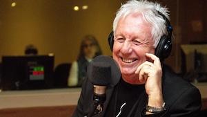 Un homme d'une soixantaine d'années sourit devant un micro.
