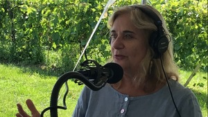 Nathalie Petrowski parle dans un micro de radio, avec des vignes derrière elle.