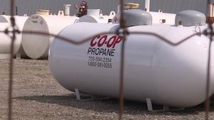 Des réservoirs de propane entreposés derrière un grillage.