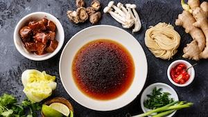 Divers ingrédients étalés sur une comptoir gris : gingembre, échalotes, champignons, etc.