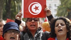 Une femme tient dans ses mains le drapeau tunisien. Le drapeau est rouge et blanc. À ses côtés, deux femmes portent du rouge.