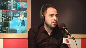 Un homme est assis devant un micro dans une studio de radio.
