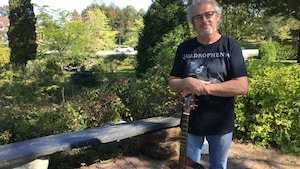 Jean Rousseau, ancien député de Compton-Stanstead et musicien. On le voit debout dans un jardin, appuyé sur sa guitare.
