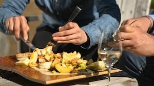Deux personnes dégustent une salade préparée sur le barbecue. Il y a un verre de vin sur la table.