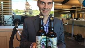 Sébastien Roy est assis en studio et tient deux bouteilles de bière.
