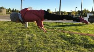 Une femme en équilibre à l'horizontale avec les mains sur un câble tendu à un mètre du sol