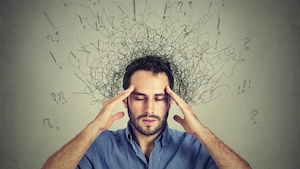 Un homme porte ses mains à la tête. Des gribouillages comportant des points d'interrogation et d'exclamation entourent sa tête.