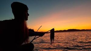 Une participante du camp Primitif pêche des maquereaux de façon rudimentaire.