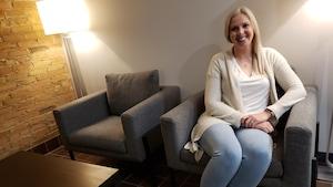 Tara Babineau, trésorière de l'Association des paramédics du Nouveau-Brunswick est assise dans un fauteuil gris.